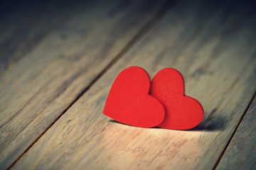 Close up of two red hearts on wooden table.
