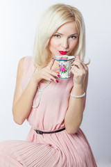 elegant girl with red lipstick in retro style drinks tea