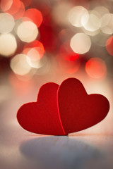 Close up of two red hearts on wooden table against defocused lig