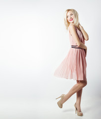 beautiful woman with bright makeup in pink dress with long legs