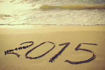 2015 year written on sandy beach. Toned image