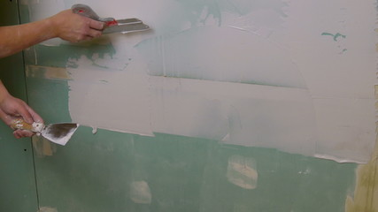 Construction Worker Applying Plaster on a Drywall, closeup