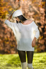 Beautiful sexy girl in white posing in park in autumn day