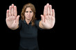 Serious woman gesturing to stop isolated on black