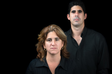 Serious hispanic man and woman isolated on black