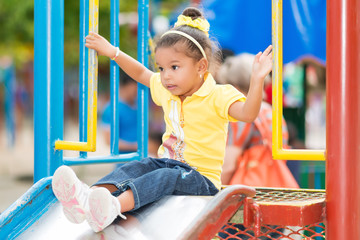 Small mixed race girl using a slide at a playground