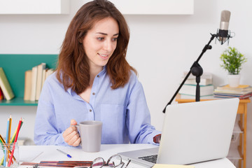 Young woman working with laptop in her workspace.