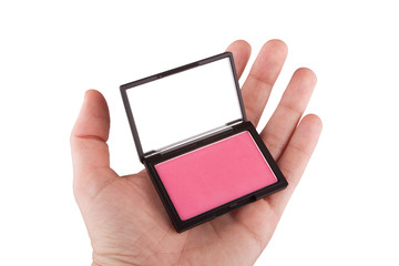 Female hand holding a pink blush, isolated on white