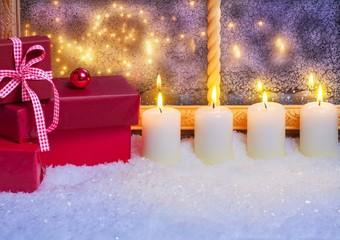 Geschenke und Kerzen im Fenster