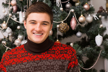 Handsome young man in front of a Xmas tree