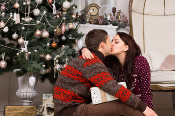 Romantic couple kissing in front of a Xmas tree
