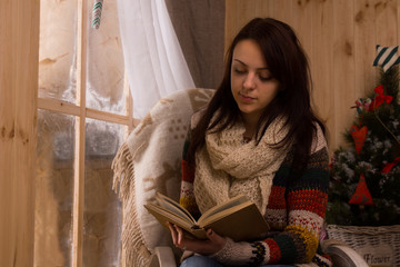 Attractive young woman sitting reading