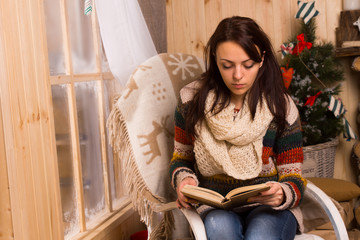 Young woman sitting reading at Christmas