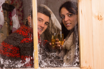 Couple Holding Glasses of Wine Behind Glass Window