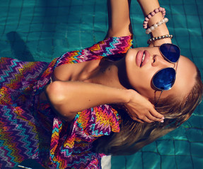 sexy blond woman in sunglasses in swimming pool