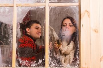 Young couple celebrating in a winter cabin