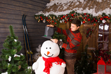 Young Man Putting Black Hat on Indoor Snowman
