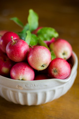 Fresh red apples with leaves in a bowl