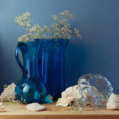 Still life with blue glass vases and seashells