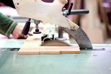 wood factory worker cutting wood boards with sliding saw
