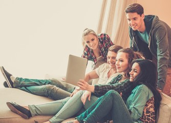 Group of young friends taking selfie in home interior