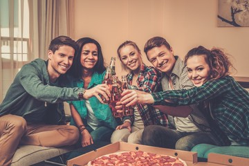 ulti-ethnic friends with pizza and bottles of drink celebrating