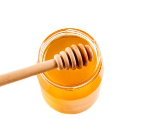 opened honey jar on white background with wooden dipper
