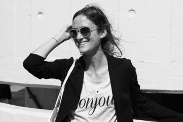 Profile of smiling model wearing sunglasses and casual jacket