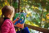 Little painter at work near waterfall