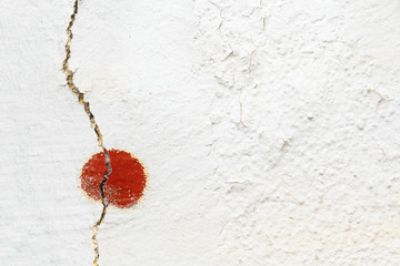 Old cracked plastered white wall with red detail