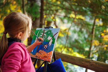 Little painter at work near waterfall