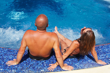 Romantic couple relaxing near pool