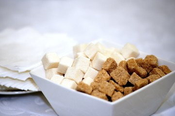 Brown and white refined sugar in square bowl with napkins