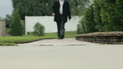Man walks towards camera on path