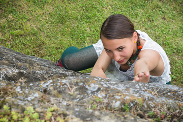 young girl climging a rock