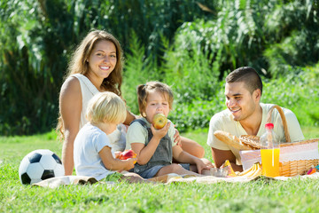 Happy family of four having picnic