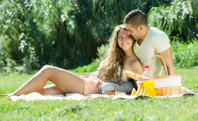 Happy  romantic couple sitting on grass at picnic