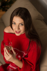 Woman wearing sweater sitting on sofa near Christmas Tree