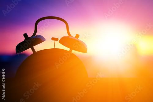 Leinwandbild Motiv alarmclock silhouette at sunrise cityscape