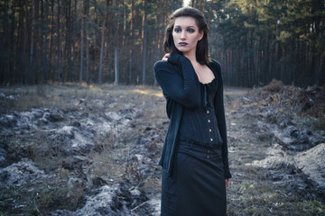 Young pensive goth woman in a autumn forest