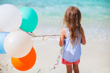 Back view of little girl with balloons at beach