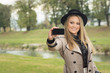 Young woman taking a selfie in park in autumn. No retouch