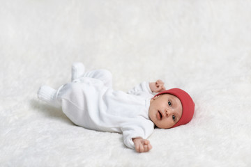 newborn baby lying on white