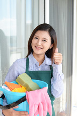 掃除用品を持つ笑顔の女性