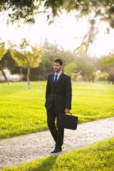 businessman walking at the city garden