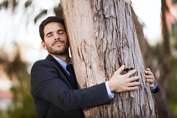Businessman embrace a tree trunk