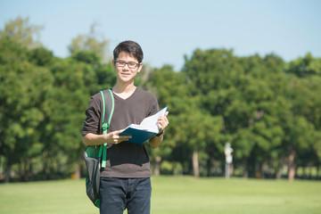 Handsome boy holding an open book, read background summer green