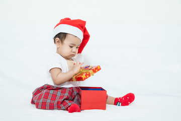 Asian baby with christmas cap opening gift box