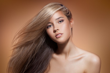 Beautiful Blond Girl. Healthy Long Hair. Brown Background