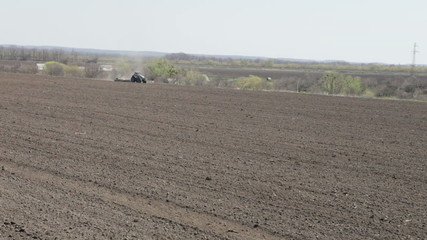 tractor rides through the black earth's field on a sunny day in